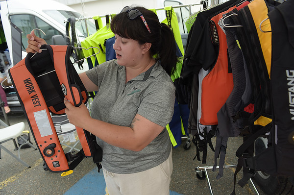 TIM JEAN/Staff photo<br /> <br /> Erin Lally, Field Research Coordinator at Northeast Center for Occupational Health and Safety talks about an Automatic Inflation work vest at the Lifejackets for Lobstermen campaign tent at the Jodrey State Fish Pier in Gloucester.  7/17/19