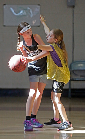 MIKE SPRINGER/Staff photo<br /> Ten-year-old Jocelyn Maddalena, left, keeps the ball away from Nae-Nae Weaver, 10, during a scrimmage Tuesday in the Cape Ann Basketball Clinic at Rockport High School.<br /> 6/16/2019