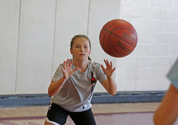 MIKE SPRINGER/Staff photo<br /> Twelve-year-old Gemma Jusseaume takes part in a passing drill Tuesday during the Cape Ann Basketball Clinic at Rockport High School.<br /> 6/16/2019