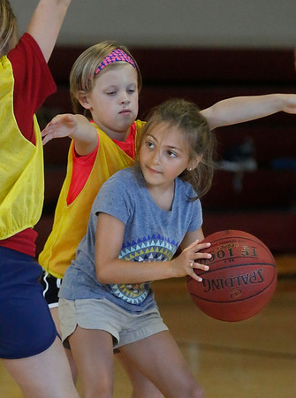 MIKE SPRINGER/Staff photo<br /> Eight-year-old River Martin looks for someone to pass the ball to as Sunny Gallagher, 9, applies defensive pressure during the Cape Ann Basketball Clinic at Rockport High School.<br /> 6/16/2019