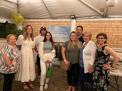 """GAIL McCARTHY/Staff photo/The atmosphere was upbeat following the local screening and premiere of the Sundance Award-winning film """"CODA,"""" set in Gloucester. Celebrating at a reception at Mile Marker One are, from left, Angela Sanfilippo, """"CODA"""" director and writer Sian Heder, Leonardo Vitale, Ava Vitale, Aislinn Vitale, Capt. Paul Vitale, Rosalie Vitale and Nina Groppo."""