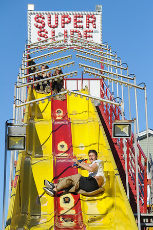 AMANDA SABGA/ Staff photo <br /> <br /> Anthony Curcuru, 14 of Gloucester, rides down the Super Slide at the Fiesta Shows carnival during the annual Gloucester St. Peter's Fiesta<br /> <br /> <br /> 6/22/16