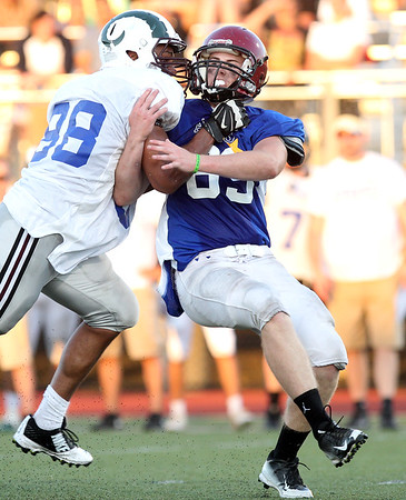 DAVID LE/Staff photo. Gloucester defensive lineman John Philpott tries to get through the grip of Lynn English lineman Jeremy Garcia while rushing the quarterback. 6/30/16.
