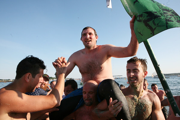 Kyle Barry is carried ashore after grabbing the flag and winning the Greasy Pole contest on Sunday.