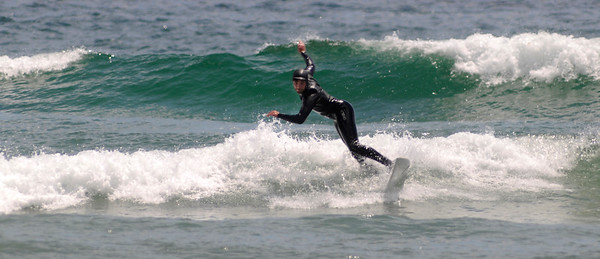 PAUL BILODEAU/Staff photo. A surfer navigates a wave at Good Harbor Beach in Gloucester.