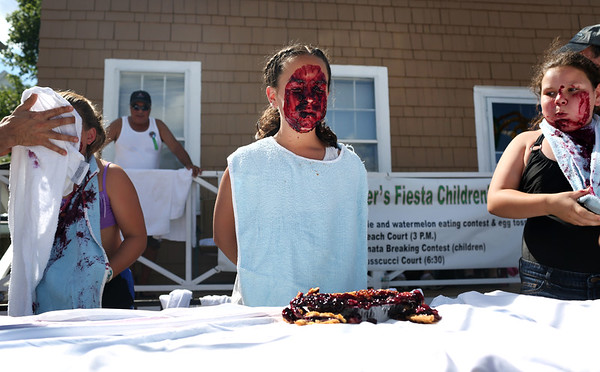 HADLEY GREEN/ Staff photo<br /> Molly Taormina, center, of Gloucester, is covered in pie after the pie eating contest at St. Peter's Fiesta on Saturday in Gloucester. 6/23/17