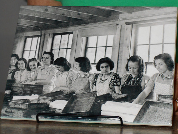 SEAN HORGAN/Staff photo<br /> One of xxx's tiles, which shows women packing fish in the mid 1940s.