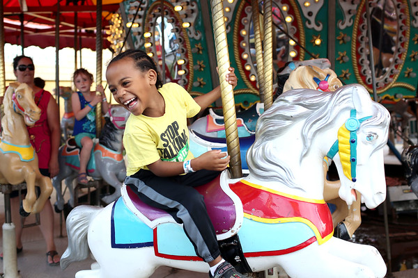 HADLEY GREEN/ Staff photo<br /> Jack Baez, 6, of Gloucester, smiles at his mom as he passes around on the carousel at the carnival for St. Peter's Fiesta in Gloucester. 6/22/17