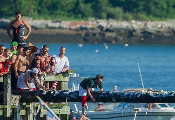 AMANDA SABGA/Staff photo<br /> <br /> Competitors try their luck during Friday night's St. Peter's Fiesta's Greasy Pole walk at Gloucester's Pavilion Beach. <br /> <br /> 6/29/18