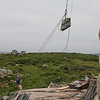 MIKE SPRINGER/Staff photo<br /> Kim Keat of Lowell pulls a rope as he and other workers with the Buffalo, New York-based International Chimney Corporation hoist a 400-pound granite block back up to the top of the north lighthouse Wednesday at Thacher Island in Rockport.  The stone fell in 2016. Workers replaced the stone and are installing metal bands around the lantern deck and the gallery deck to prevent more stones from falling.<br /> 6/27/2018