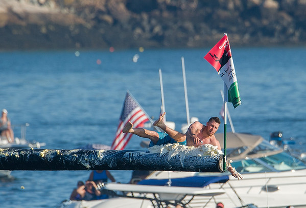 AMANDA SABGA/Staff photo<br /> <br /> Frank Taormina reaches for the flag, which he retrieved, during Friday night's St. Peter's Fiesta's Greasy Pole competition at Gloucester's Pavilion Beach. <br /> <br /> 6/29/18