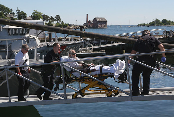 MIKE SPRINGER/Staff photo A lobsterman from the Gloucester-based Sea Force 1 is wheeled up the ramp at Coast Guard Station Gloucester on Tuesday by Gloucester firefighter/EMTs after he was rescued 12 miles offshore. 6/19/2018