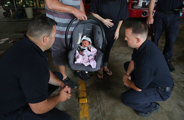 MIKE SPRINGER/Staff photo<br /> Gloucester firefighter-paramedics Mike Mitchell, left, and Andrew Lyons look at newborn Selah Goulart on Monday at Gloucester Fire Department Headquarters. Mitchell and Lyons were part of a team of firefighter-paramedics who helped with Selah's birth June 19 in the kitchen of her family's home.<br /> 6/25/2018