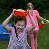 MIKE SPRINGER/Staff photo<br /> Fourth-grader Katy Hautala carries a wet sponge above her head while competing in a relay race Friday during the annual year-end field day celebration at East Gloucester Elementary School. Parent volunteers organized a variety of games for the students to play.<br /> 6/15/2018