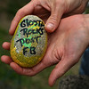 "MIKE SPRINGER/Staff photo<br /> Aria McElhenny shows the backside of a ""Glosta Rock,"" which asks finders to log onto a Facebook page.<br /> 6/14/2018"