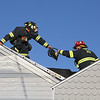 MIKE SPRINGER/Staff photo<br /> Essex firefighter Jon O'Bryan, left, hands a chainsaw to Lt. David Thompson as they prepare to cut through the roof during firefighting exercise Tuesday at the former Fortune Palace restaurant in Essex. The new owner of the building, John Collins of Hamilton, offered the fire department the opportunity to use the structure for training before it is torn down to make way for a new business.<br /> 6/19/2018