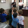 ANDREA HOLBROOK/Staff photo/Essex Police Patrolman Daniel J. Bruce, left, and Chief and Harbormaster Peter G. Silva take questions from Essex Elementary School kindergartners who toured the Martin Street police station and harbormaster's office on Tuesday morning.
