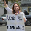 MIKE SPRINGER/Staff photo<br /> Renee Gauthier, protective services director for SeniorCare, waves to passing motorists during the annual elder abuse awareness rally Thursday on Rogers Street in Gloucester. The event, sponsored by SeniorCare, the Gloucester Police Department and the Gloucester Council On Aging, included a free cook-out with food donated by local businesses and grilled by police officer.<br /> 6/7/2018