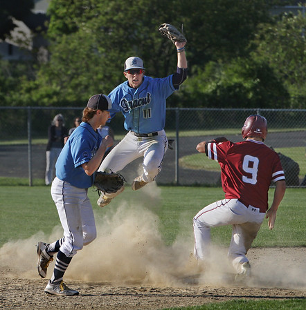 MIKE SPRINGER/Staff photo<br /> Dracut second baseman John Cormier, center, jumps in the air after forcing out Gloucester's Matthew Smith in the seventh inning to win the Division 3 North baseball quarterfinals Monday in Gloucester. At left is Dracut shortstop Kyle Hould. Dracut won the game, 3-2.<br /> 6/11/2018