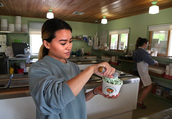 MIKE SPRINGER/Staff photo<br /> Mia Ciavola, manager of DownRiver Ice Cream in Essex, scoops ice cream into a compostable cup.<br /> 6/15/2018 [[MER1806151853320726]]