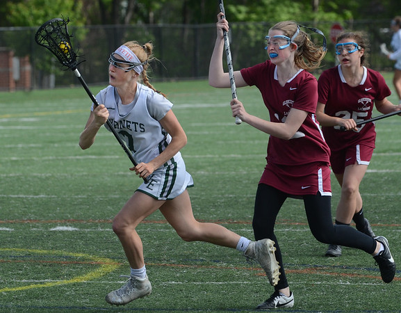 MIKE SPRINGER/Staff photo<br /> Abigail Lantz of Manchester Essex carries the ball past Annarita Sanfilippo, right, and Madison Vittands, far right, during Division 2 lacrosse first round tournament play Tuesday in Manchester.<br /> 6/5/2018