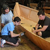 MIKE SPRINGER/Staff photo<br /> Eighth-grader Tyler Johnson, center, drills a hole in the side of a row boat as classmate Logan Benway, right, and instructor Zack Teal look on Thursday at the Essex Shipbuilding Museum. All 45 eighth-graders in the Beach House section of O'Maley Innovation Middle School participated in a two-day boat-building project at the museum that began Wednesday. Under the supervision of STEM specialist Dave Brown and science coordinator Amy Donnelly, and with help from Teal and other instructors at the shipbuilding museum, the students built two 24-foot, flat-bottomed Sharptown Barges and two sets of oars. Donnelly said she hopes to use the two boats built this year and the ones built last year as a fleet for educational outings in the future, such as the annual sixth-grade marsh science project.<br /> 6/14/2018