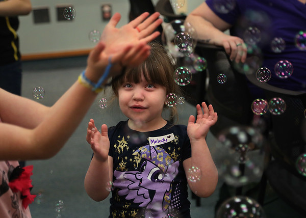 """MIKE SPRINGER/Staff photo<br /> Five-year-old Melody Rodgers joins other children in trying to catch bubbles from a bubble machine during a """"Rainbow"""" storytime and craft event Friday at the Sawyer Free Library.<br /> 6/22/2018"""