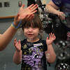 "MIKE SPRINGER/Staff photo<br /> Five-year-old Melody Rodgers joins other children in trying to catch bubbles from a bubble machine during a ""Rainbow"" storytime and craft event Friday at the Sawyer Free Library.<br /> 6/22/2018"