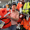"""MIKE SPRINGER/Staff photo<br /> Skip Sheppard, owner of Three Lantern Marine & Fishing, holds a life jacket  in his store Tuesday. The shop carries a full line of safety equipment, including life jackets, buoys, rafts, beacons, flare guns, first aid kits -- """"everything you would need for safety on a boat,"""" says Sheppard.<br /> 6/5/2018"""