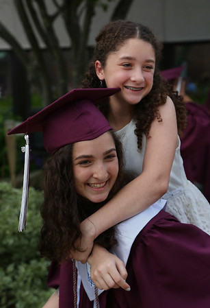MIKE SPRINGER/Staff photo<br /> Graduating senior Emma Sekercan holds her 12-year-old sister Julia on her shoulders while posing for photos before the start of the 2018 graduation ceremony Friday at Rockport High School. Sixty-seven seniors graduated.<br /> 6/1/2018
