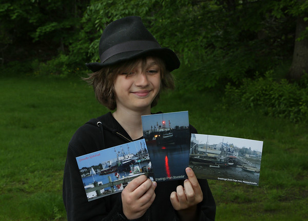 """MIKE SPRINGER/Staff photo<br /> Thirteen-year-old entrepreneur Zachary Malott of Gloucester holds a few postcards from his new enterprise, """"Zach's Post Card Company."""" The O'Maley Middle School student has already made a name for himself by self-publishing a series of photo books, including """"Let's Explore Gloucester."""" He plans to market his new line of postcards through area businesses and donate a portion of the profits to charity."""