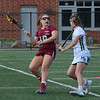 MIKE SPRINGER/Staff photo<br /> Gloucester's Ruby Melvin, right, looks for someone to pass to beyond Bridget Twombly of Manchester Essex during Division 2 lacrosse first round tournament play Tuesday in Manchester.<br /> 6/5/2018