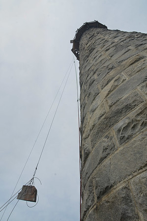 MIKE SPRINGER/Staff photo<br /> A 400-pound block of granite is hoisted up to the top of the north lighthouse Wednesday at Thacher Island. The stone fell from the tower in 2016.<br /> 6/27/2018