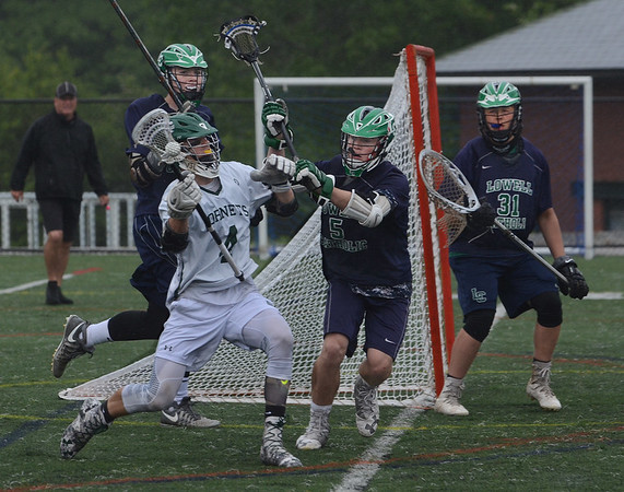MIKE SPRINGER/Staff photo<br /> Jake Athanas, left, of Manchester Essex brings the ball around the net as Michael Andrea and goalie Kyle Knight play defense for Lowell Catholic during Division 3 North first round lacrosse playoff action Monday in Manchester.<br /> 6/4/2018