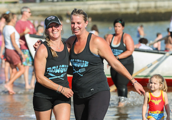 Staff photo/ HADLEY GREEN<br /> <br /> From left, Rowgue teammates Alex Pizzimenti and Emily Silva embrace after winning the women's seine boat race during Friday night's Fiesta celebration at Pavilion Beach in Gloucester.<br /> <br /> 06/29/2018