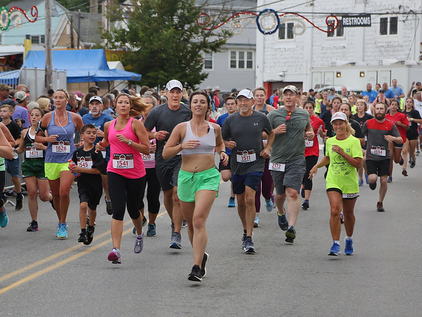 MIKE SPRINGER/Staff photo Runners pass St. Peter's Square during the Fiesta 5K Road Race Thursday evening in Gloucester. 6/28/2018
