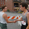 MIKE SPRINGER/Staff photo<br /> First-place winner Mike Darnell, left, of Brooklyn, New York shakes hands with second-place finisher Willy Pierce of Gloucester Thursday evening at the finish line of the Fiesta 5K Road Race in Gloucester.<br /> 7/28/2018