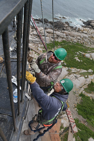 MIKE SPRINGER/Staff photo<br /> Roy Fischer, above, of Buffalo New York and Kim Keat of Lowell work on a scaffolding near the top of the north lighthouse on Thacher Island to restore a 400-pound block that fell from the tower in 2016.<br /> 6/27/2018