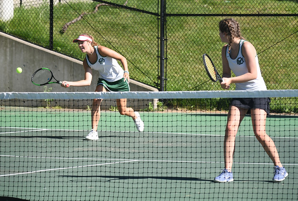 JIM VAIKNORAS/Staff photo Manchester-Essex Chanel Bollock returns a shot against Ursuline Academy she is playing alongside her sister Christina in the 1st doubles match at Newton North High school Tuesday.