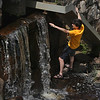 MIKE SPRINGER/Staff photo<br /> Eighth grader Connor Dench reaches out to touch the water near its point of maximum potential energy and minimum kinetic energy as part of a lesson in the physics of waterfalls during the annual Millbrook Watershed Field Trip on Tuesday in Rockport.<br /> 6/12/2018
