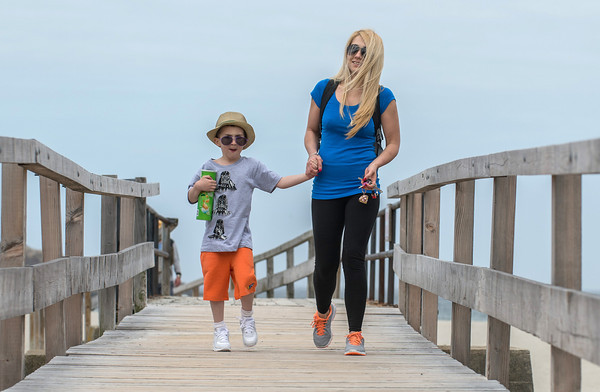 DESI SMITH/Staff photo.     Doprota Ferrara of Gloucester, walks over the Good Harbor Beach foot bridge with her son Giacomo 6, after spending some time together on the beach Thursday afternoon as they head back back to the car.  May 15,2014