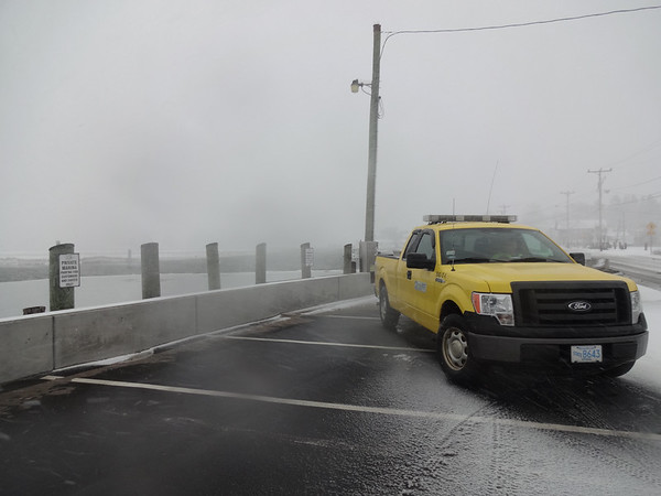 MARY MARKOS/Staff photo<br /> A state Department of Transportation worker monitors the Essex Causeway , also Main Street and Route 133, as the tide rises around noon Tuesday. The estuary Essex River did not rise enough to flood the roadway, and officials the same would hold true for the evening high tide.