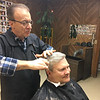 RAY LAMONT/Staff photo<br /> Sal Palazzola gives a trim to customer David Hepworth of Rockport at Sal's Barber Shop on Main Street in Gloucester on Tuesday morning as the storm started.