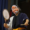 MIKE SPRINGER/Staff photo<br /> Juni Kobayashi of Lexington plays a fan drum while wearing a mask Thursday at East Gloucester Elementary School. Kobayashi and Elaine Fong of Brookline, both members of the Woburn-based group Odaiko New England, visited the school to perform and to explain how taiko drums are in many aspects of traditional Japanese culture.<br /> 3/29/2018
