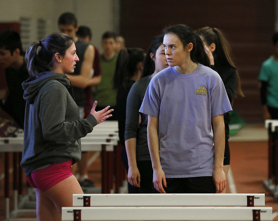 MIKE SPRINGER/Staff photo<br /> Senior co-captain Kaitlin Marques, left, talks with junior Diane Story about a drill during the first day of track practice Monday at Gloucester High School.<br /> 3/19/2018
