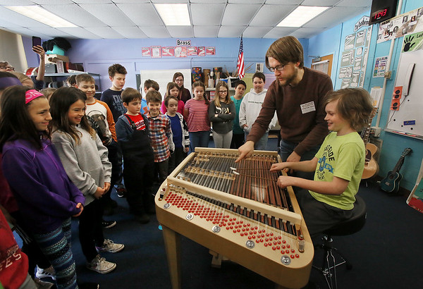 MIKE SPRINGER/Staff photo<br /> Musician Nick Tolle of Lowell shows fourth-grader Albenie Sperry how to play a cimbalom as his classmates look on Tuesday at Rockport Elementary School. The cimbalom is an elaborate stringed instrument of the dulcimer family used by central European Roma (Gypsies). Tolle's visit was organized by Rockport Music in part to familiarize members of the Rockport High School orchestra with the instrument in preparation for their April vacation trip to Eastern Europe. Tolle will return for a residency and concert in May.<br /> 3/20/2018