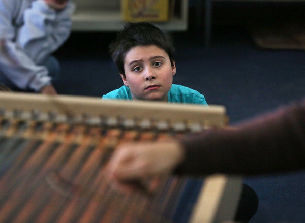 MIKE SPRINGER/Staff photo<br /> Fourth-grader Ayden Sweet watches Nick Tolle of Lowell play a cimbalom Tuesday at Rockport Elementary School. The cimbalom is an elaborate stringed instrument of the dulcimer family used by central European Roma (Gypsies). Tolle's visit was organized by Rockport Music in part to familiarize members of the Rockport High School orchestra with the instrument in preparation for their April vacation trip to Eastern Europe. Tolle will return for a residency and concert in May.<br /> 3/20/2018
