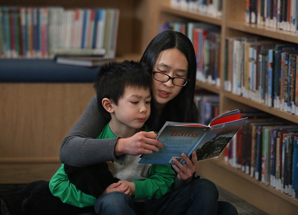 MIKE SPRINGER/Staff photo<br /> Miriam McAvoy reads a book about trains with her son Jack, 5, at the Manchester Public Library.<br /> 3/17/2018