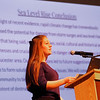 "MIKE SPRINGER/Staff photo<br /> Alex Muise, a senior, presents the conclusion of a student report, ""Consequences of Sea Leval Rise and Storm Surges as a Result of Human-Accelerated Climate Change,"" Friday in the Gloucester High School auditorium. Seniors from the school's ecology and environental issues classes conducted the study.<br /> 3/23/2018"