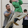MIKE SPRINGER/Staff photo<br /> Fifth-grader Jack Bediz uses all his strength to navigate the bosun chairs course as physical education teacher Greg Marche stands by to catch him during a Project Adventure lesson Monday at Essex Elementary School. Students on the bosun chairs course have to find a way to step across a series of rope-suspended chairs that are spaced at a challenging distance from each other. The purpose is to improve coordination, balance and teamwork.<br /> 3/12/2018